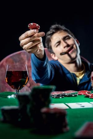 hombre fumando puro: Jugador de póquer celebración de chip de póquer
