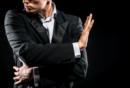 エレガントな黒のジャケットと黒の背景にポーズをとって青いシャツの男