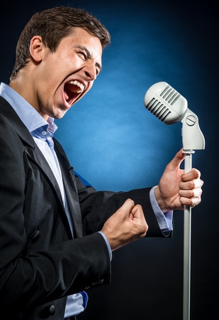 Man in elegant black jacket and blue shirt singing photo