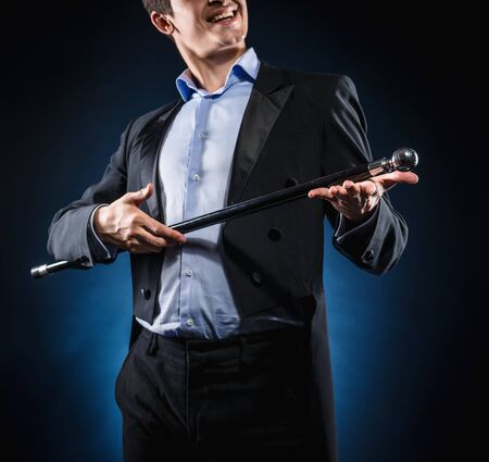 magic trick: Man in elegant black jacket and blue shirt holding cane with silver ball handle