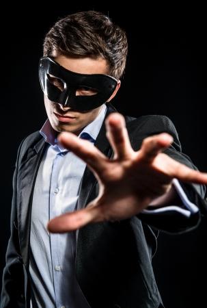 エレガントな男の身に着けている黒いマスク ポーズ屋内