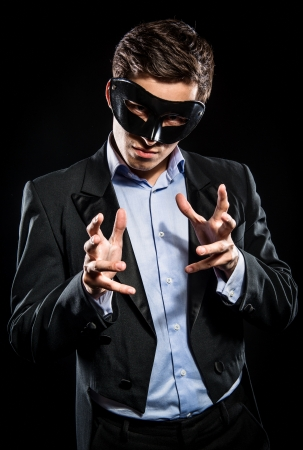 incognito: Elegant man wearing black mask posing indoors