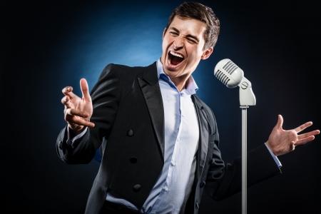 Man in elegante jaqueta preta e camisa azul cantar