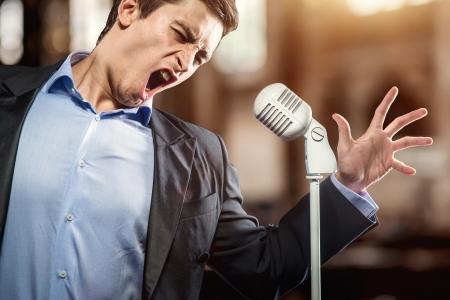 people singing: Man in elegant black jacket and blue shirt singing