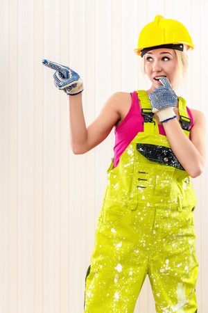 Woman wearing coverall and hard hat posing indoors photo