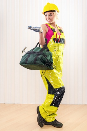 protective workwear: Female construction worker with tool bag indoors   Stock Photo