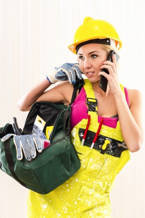 protective workwear: Female construction worker with tool bag talking by phone   Stock Photo