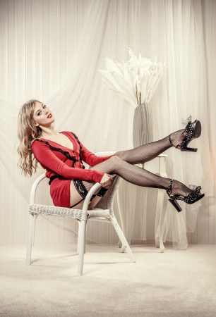 Sexy blond woman wearing black stockings and high heels posing indoors  photo