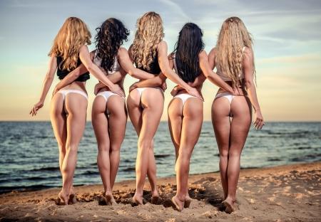 Sexy ruggen van vijf mooie vrouwen in bikini op het strand Stockfoto