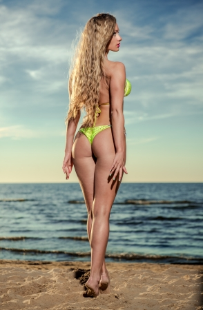 Sexy young woman with long blond hair in bikini posing on the beach photo