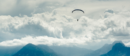 Paraglider over mountains and cloudy sky background photo