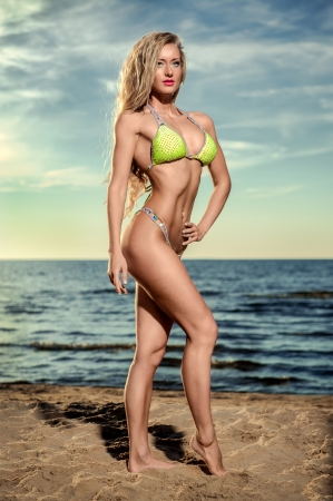 Sexy muscular build woman with long blond hair in bikini posing on the beach photo