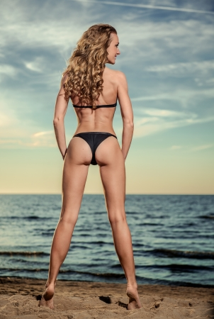 Sexy woman with long curly hair in black bikini posing on the beach photo