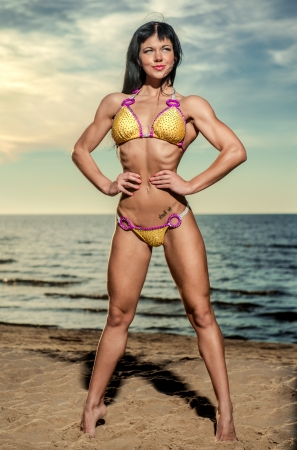 Sexy muscular build brunette in bikini posing on the beach photo