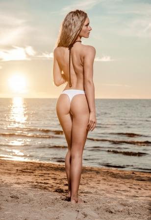 Sexy jonge vrouw met lang haar poseren op het strand bij zonsondergang
