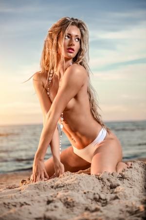 corps femme nue: Sexy jeune femme avec de longs cheveux torse nu posant sur la plage au coucher du soleil Banque d'images