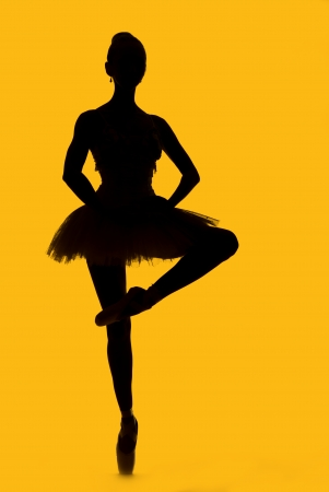 Black silhouette of ballerina isolated over yellow background photo