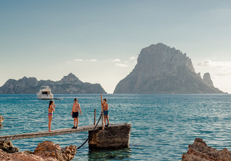 es: IBIZA, SPAIN- SEPTEMBER 22: Children in popular Cala dHort Beach on September 22. Small, beloved beach with a fantastic view of the mysterious island of Es Vedra, which lies only several hundred meters from the shore.