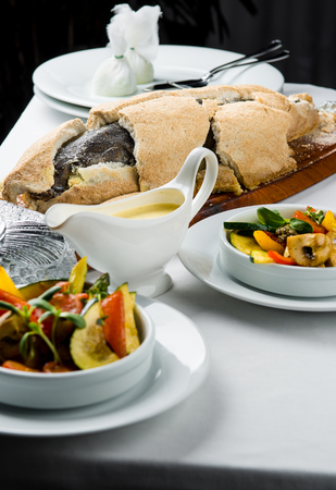 Baked whole fish in a salt crust served with vegetable salad and sauce photo