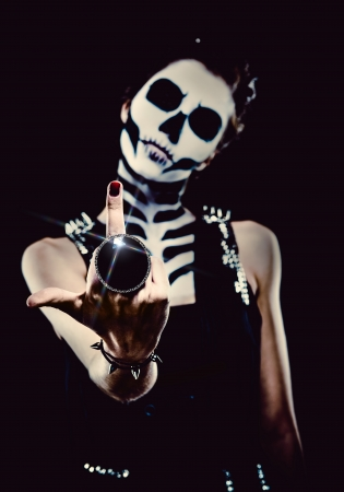Woman with skeleton face art over black background  photo