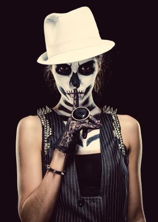 Vrouw met skelet gezicht kunst maken van een hush gebaar over zwarte achtergrond