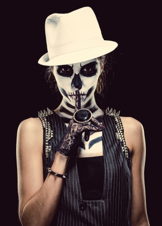 Woman with skeleton face art making a hush gesture over black background