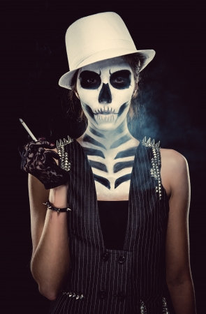 Woman with skeleton face art smoking over black background, conceptual photo photo