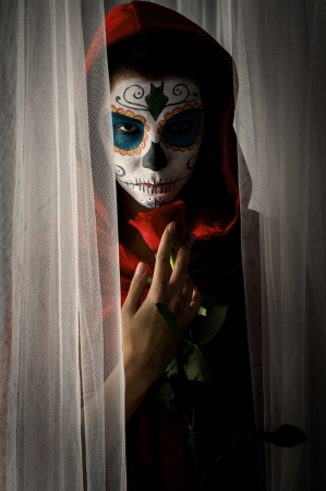 Day of the dead girl with sugar skull makeup holding red rose photo