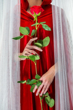 Woman wearing red cloak holding red rose photo