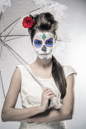 Day of the dead girl with sugar skull makeup holding lace umbrella photo