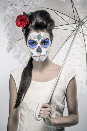 mortality: Day of the dead girl with sugar skull makeup holding lace umbrella