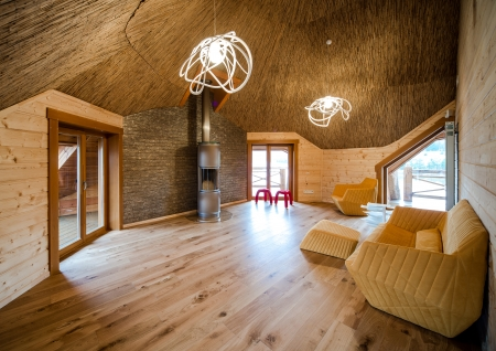 Fashionable living room with wooden floor and walls and straw ceiling
