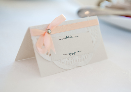 White place card decorated with orange bow photo