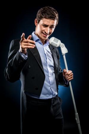 Man in een elegante zwarte jas en blauw shirt zingen
