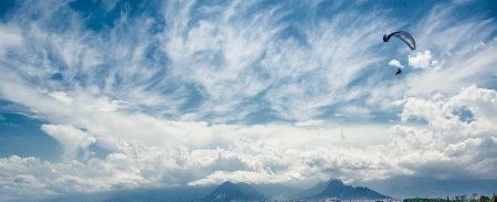 skydive: Paraglider over mountains and cloudy sky background