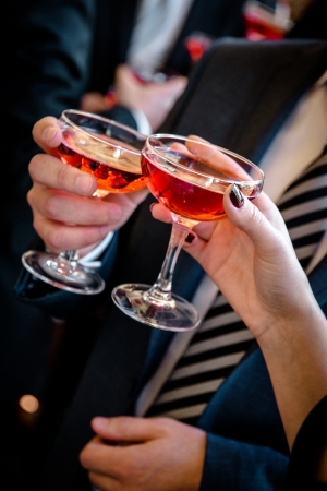 aperitif: Hands of man and woman cheering with glasses of pink champagne