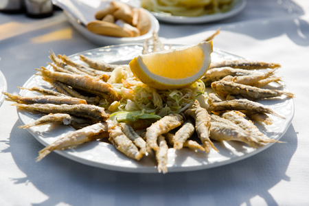 andalusian cuisine: Plate of deep fried anchovies with lemon and salad Stock Photo