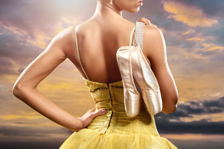Ballerina with pointe shoes against sky background photo