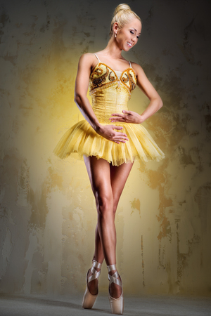 Beautiful ballerina in yellow tutu on point over obsolete wall photo