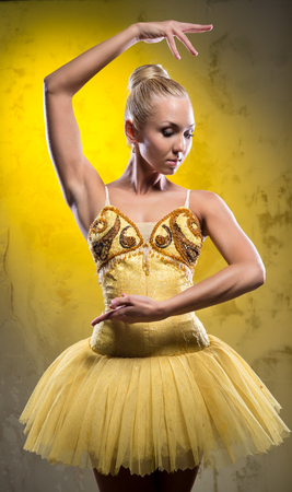 Lovely ballerina in yellow tutu posing over obsolete wall photo