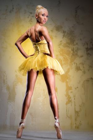 Beautiful ballerina in yellow tutu on point posing over obsolete wall photo