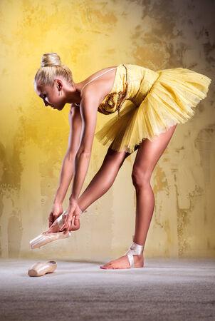 Beautiful ballerina in yellow tutu wearing pointe shoes photo