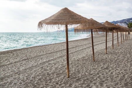 andalusia: Straw parasols on empty beach  Nerja, Spain