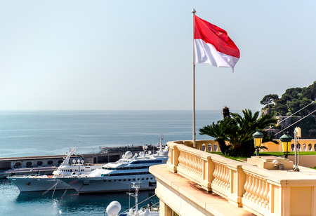 principality: National flag of of the Principality of Monaco and view of port