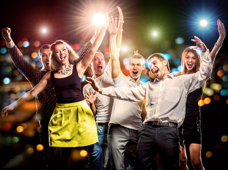 friends party: Cheerful group of young people dancing at party Stock Photo