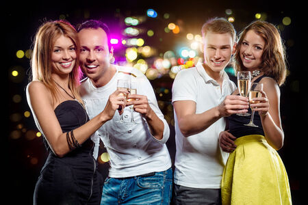 Cheerful group of young people with glasses of sparkling champagne over abstract background photo