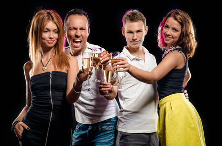 Cheerful group of young people with glasses of sparkling champagne over black background photo