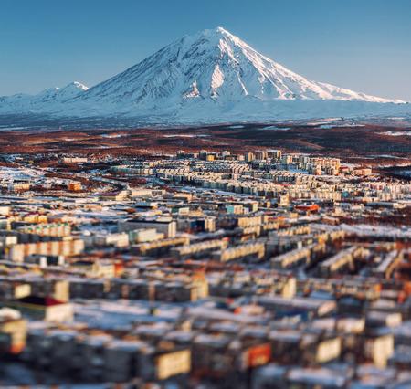 far east: Paisaje urbano Petropavlovsk de Kamchatka y el volc�n Koryaksky al amanecer Lejano Oriente, Rusia imagen con un efecto de desplazamiento de inclinaci�n Foto de archivo