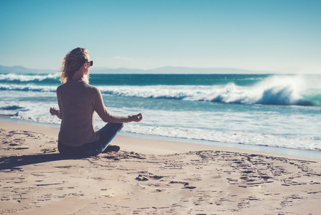 Young woman meditating on the beach  Stock Photo