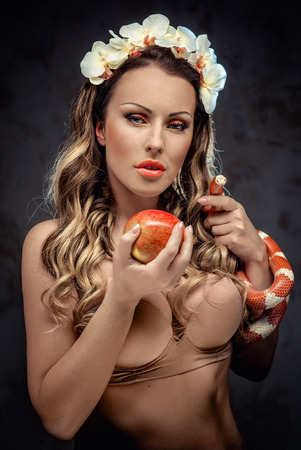 Sexy beautiful woman with red apple and snake, conceptual photo photo